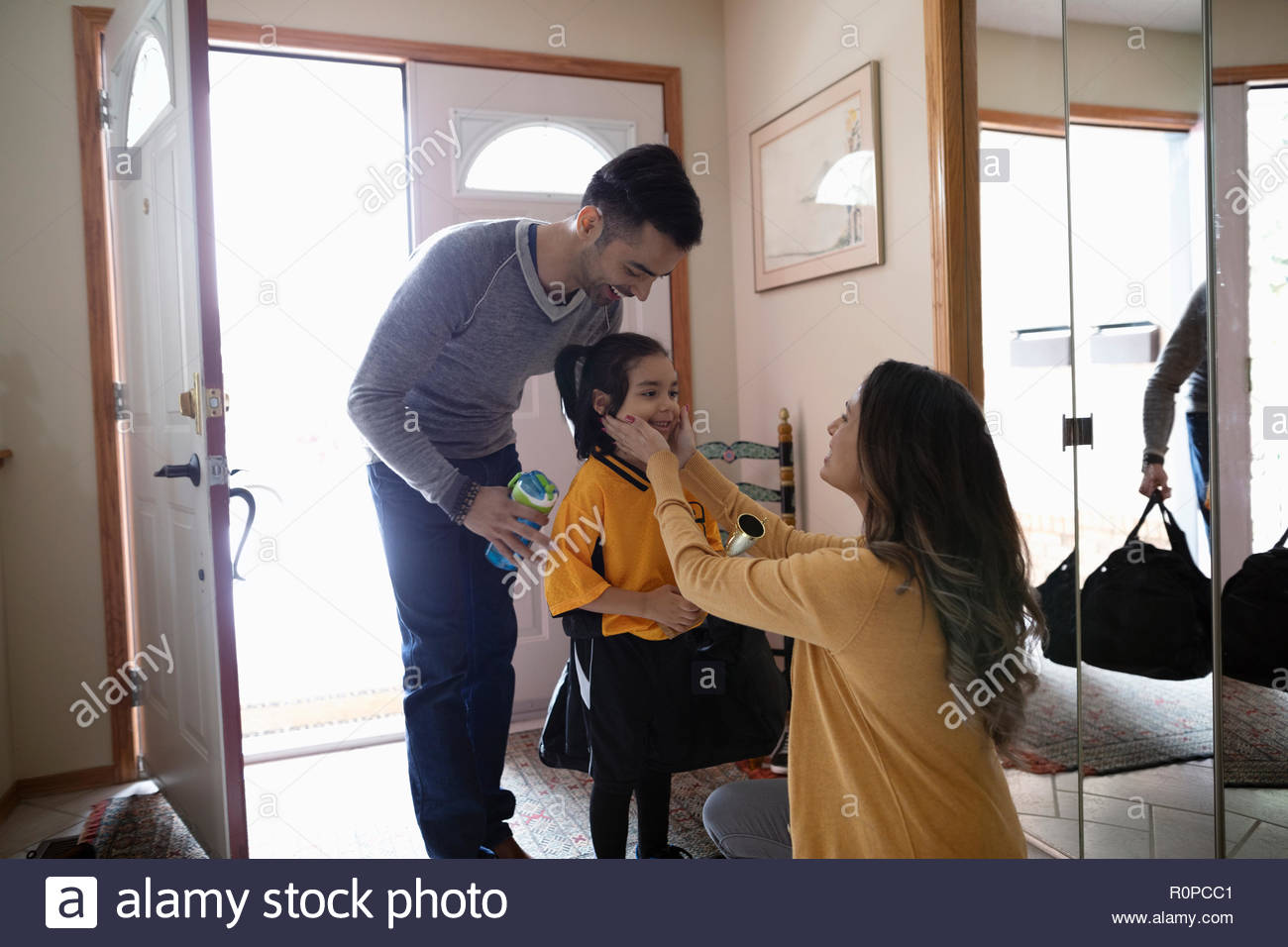 Mother saying goodbye to husband and son in soccer uniform - Stock Image