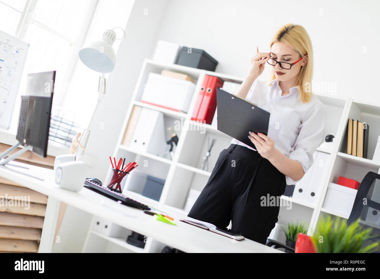 A young girl standing in the office at the computer Desk and fills out a document. - Stock Image