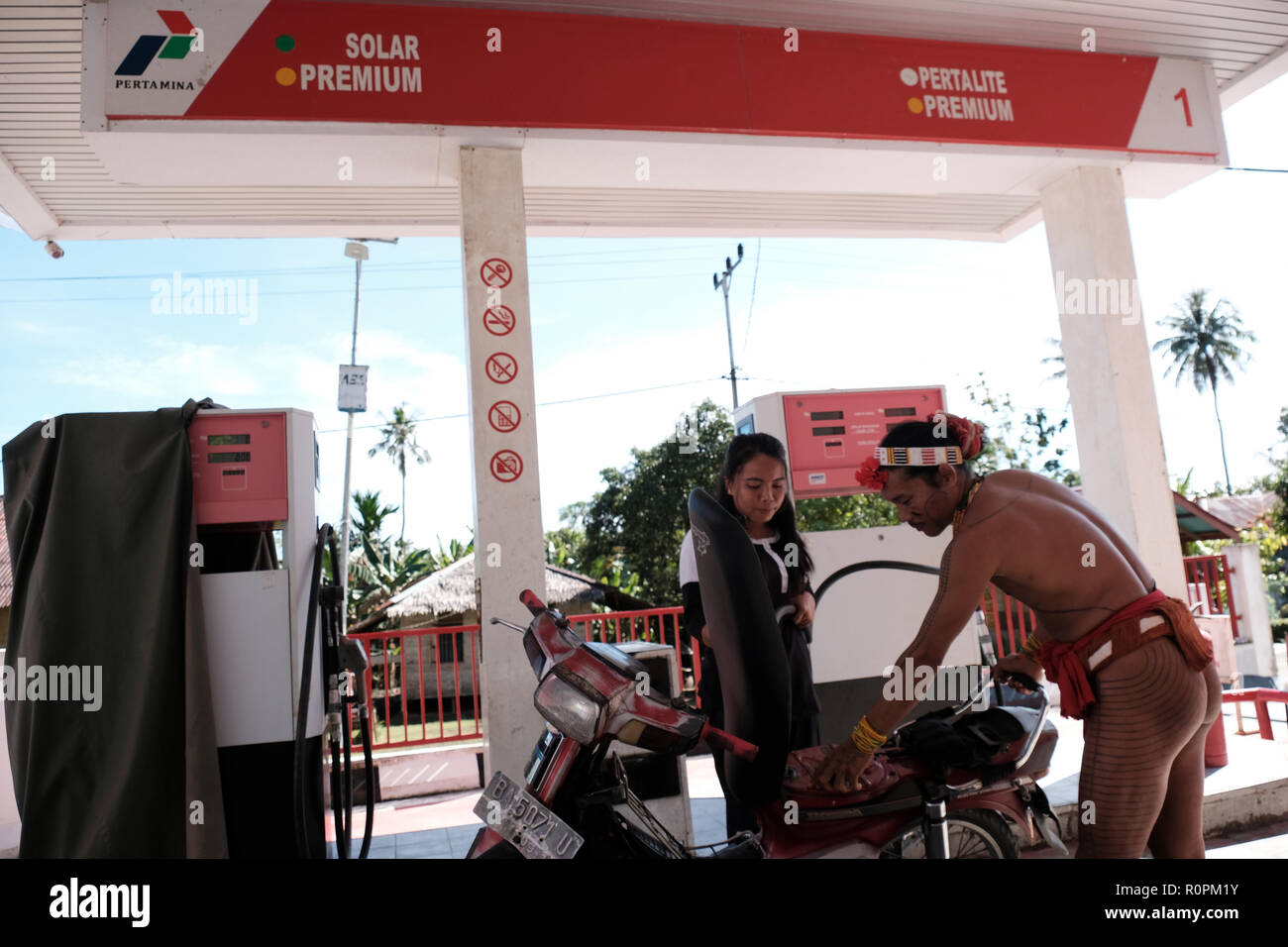 Mentawai Islands, West Sumatra, Indonesia. 3rd Nov, 2018. MENTAWAI ISLANDS, INDONESIA - NOVEMBER 07 : A Sikerei, a Mentawai shaman, is filling gasoline at the Pertamina fuel oil station on Siberut Island on November 03, 2018 in Mentawai islands, West Sumatra Province, Indonesia. The Mentawai Islands have a unique culture because they still preserve shamans called Sikerei for treatment for their people. Sikerei is dressed in minimal clothing with various leaves and flowers on the Mentawai Islands. Credit: Sijori Images/ZUMA Wire/Alamy Live News - Stock Image