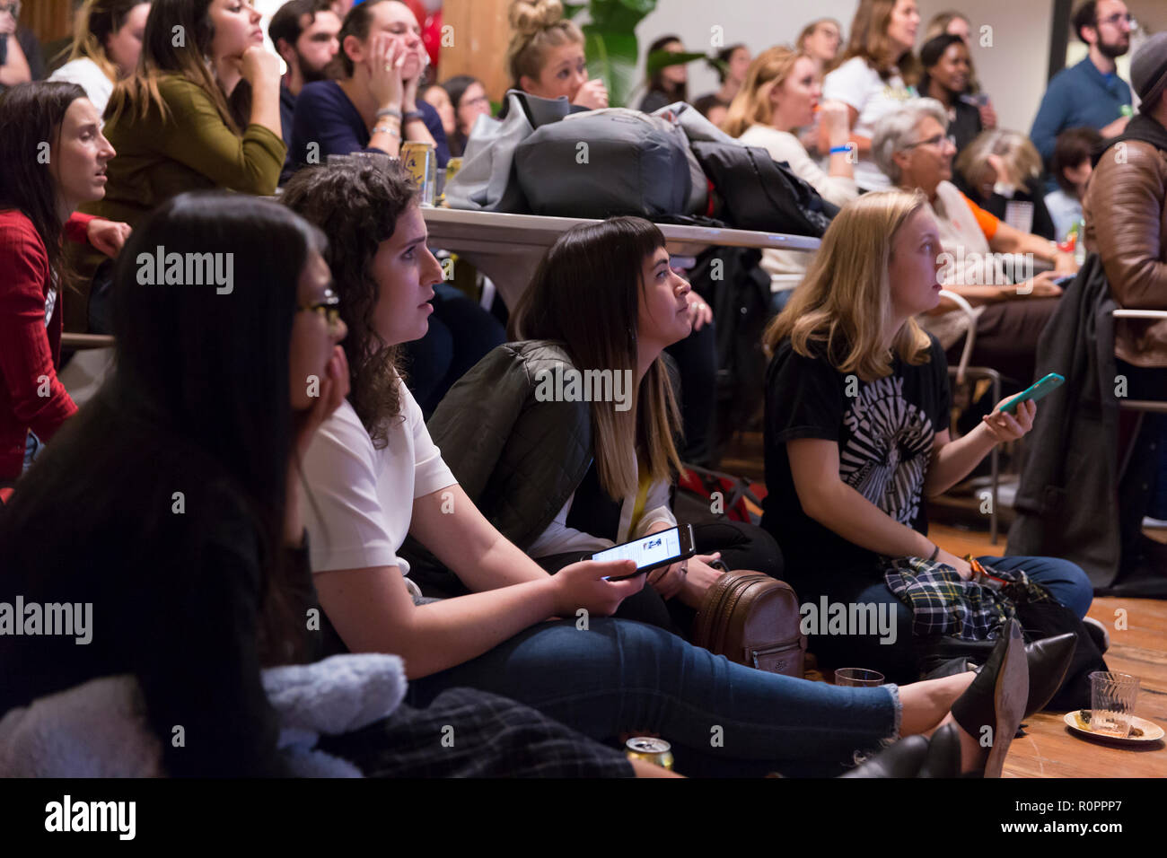"""Seattle, Washington: Supporters quietly watch live results at the election night party, """"She Came, She Saw, She F*ing Voted"""", at The Riveter in Capitol Hill. The gathering was a fundraiser for She Should Run, a non-partisan organization supporting women leaders considering a future run for office. Credit: Paul Christian Gordon/Alamy Live News - Stock Image"""
