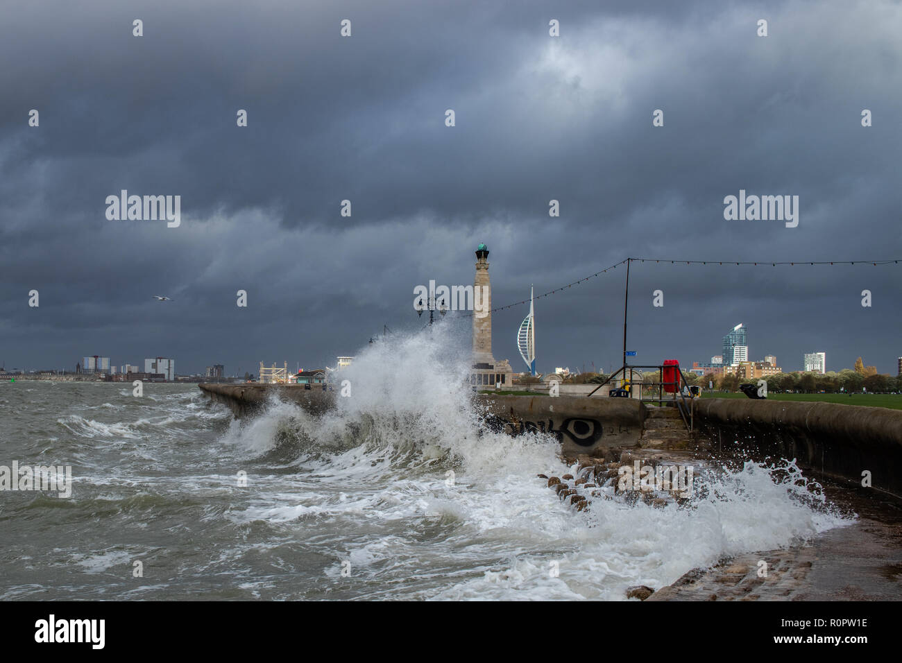Waves breaking over the sea wall at southsea during a storm, war memorial and Spinnaker tower in the background Stock Photo