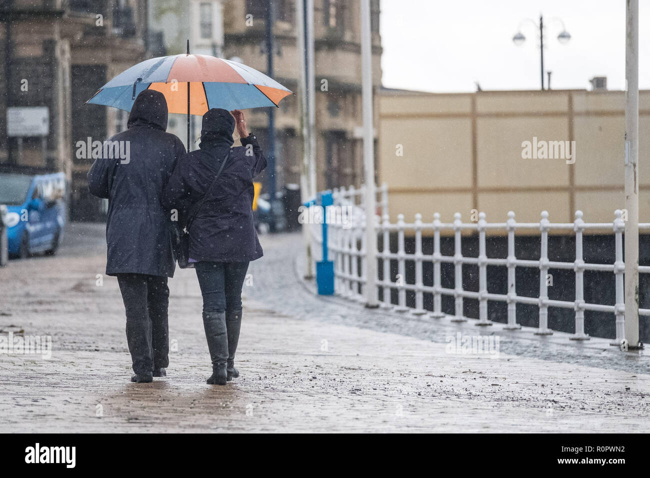 Aberystwyth, Wales, UK. 7th November, 2018.   UK Weather: People walking in the rain on a  very wet , but mild, morning in Aberystwyth. The Met Office has issued a yellow warning for rain and floods covering much of south and west wales this morning, with a further warning for more rain and gale force winds issued for the same area on Friday as well.   Photo credit: Keith Morris/ Alamy Live News - Stock Image