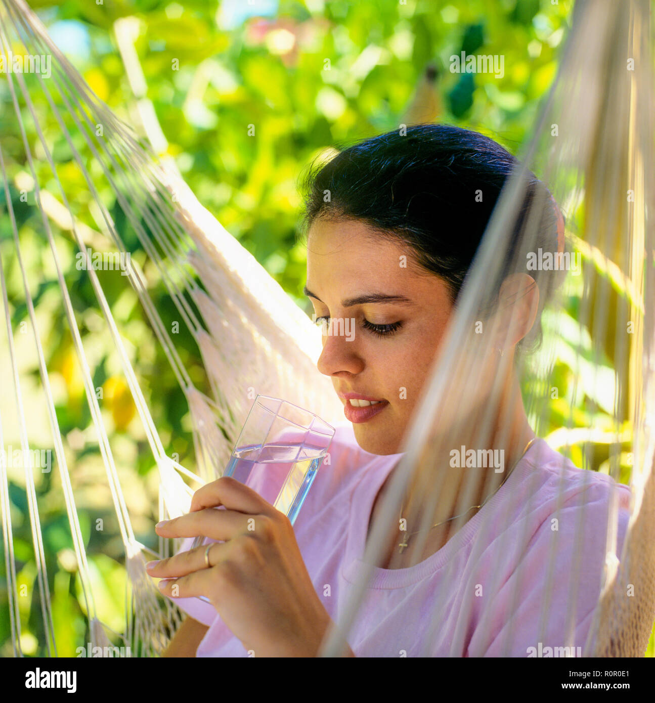Young woman holding a glass of water, tropical garden, Guadeloupe, French West Indies, - Stock Image
