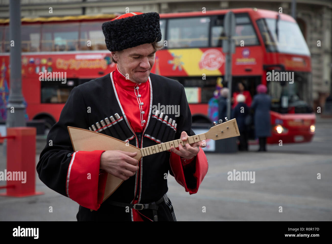 A man in a uniform of a Kuban Cossack plays a balalaika against a backdrop of the City Sightseeing tourist bus on Manezhnaya Square in Moscow, Russia - Stock Image