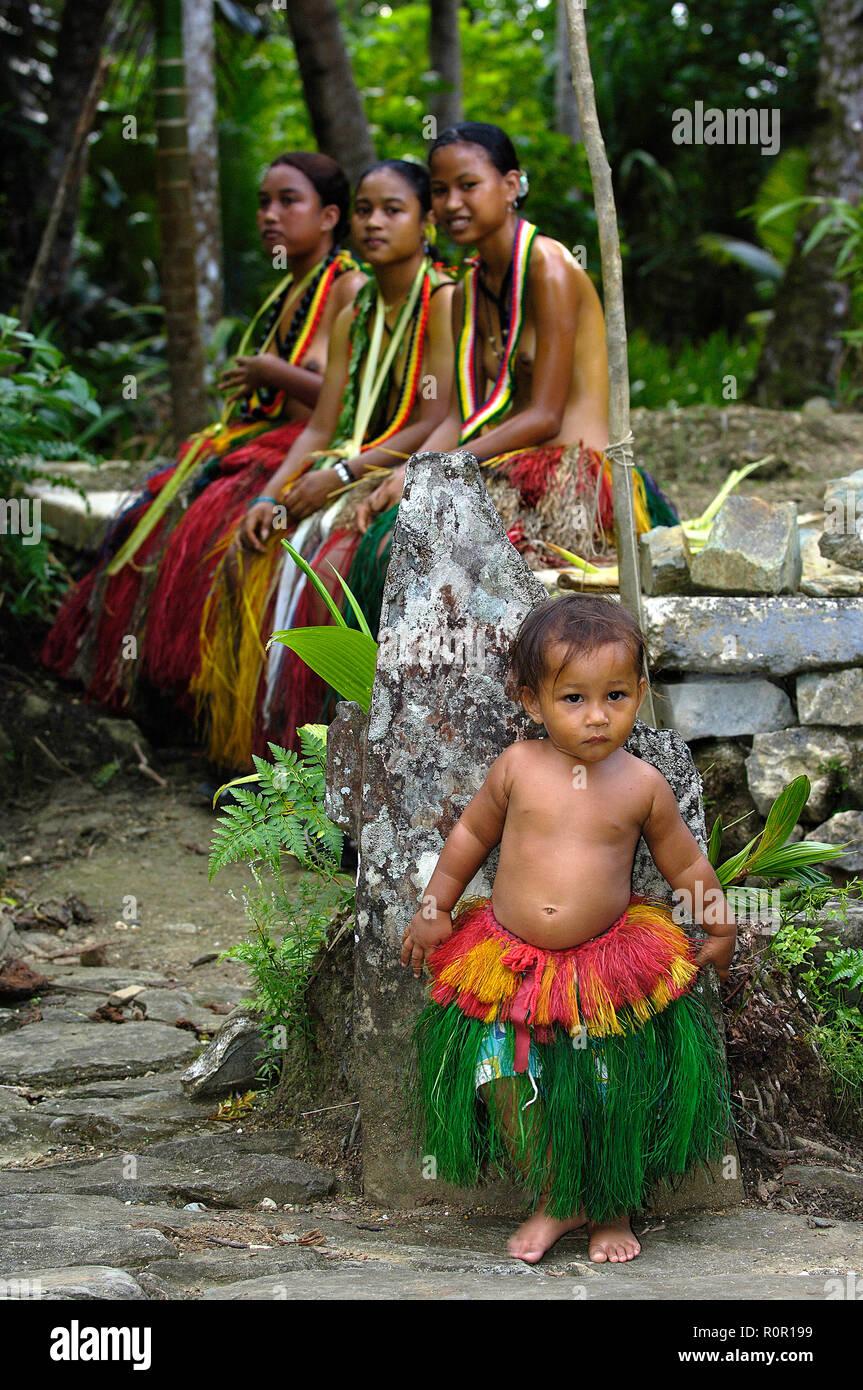 Einheimische Frauen und kleines Mädchen tragen Baströcke, Yap, Mikronesien | Traditionally dressed women with little girl wearing hula skirts, Yap, Mi Stock Photo