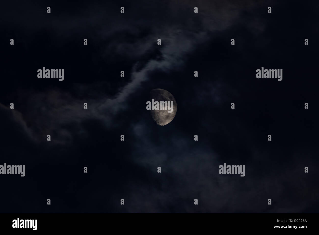 Moon behind clouds - Stock Image