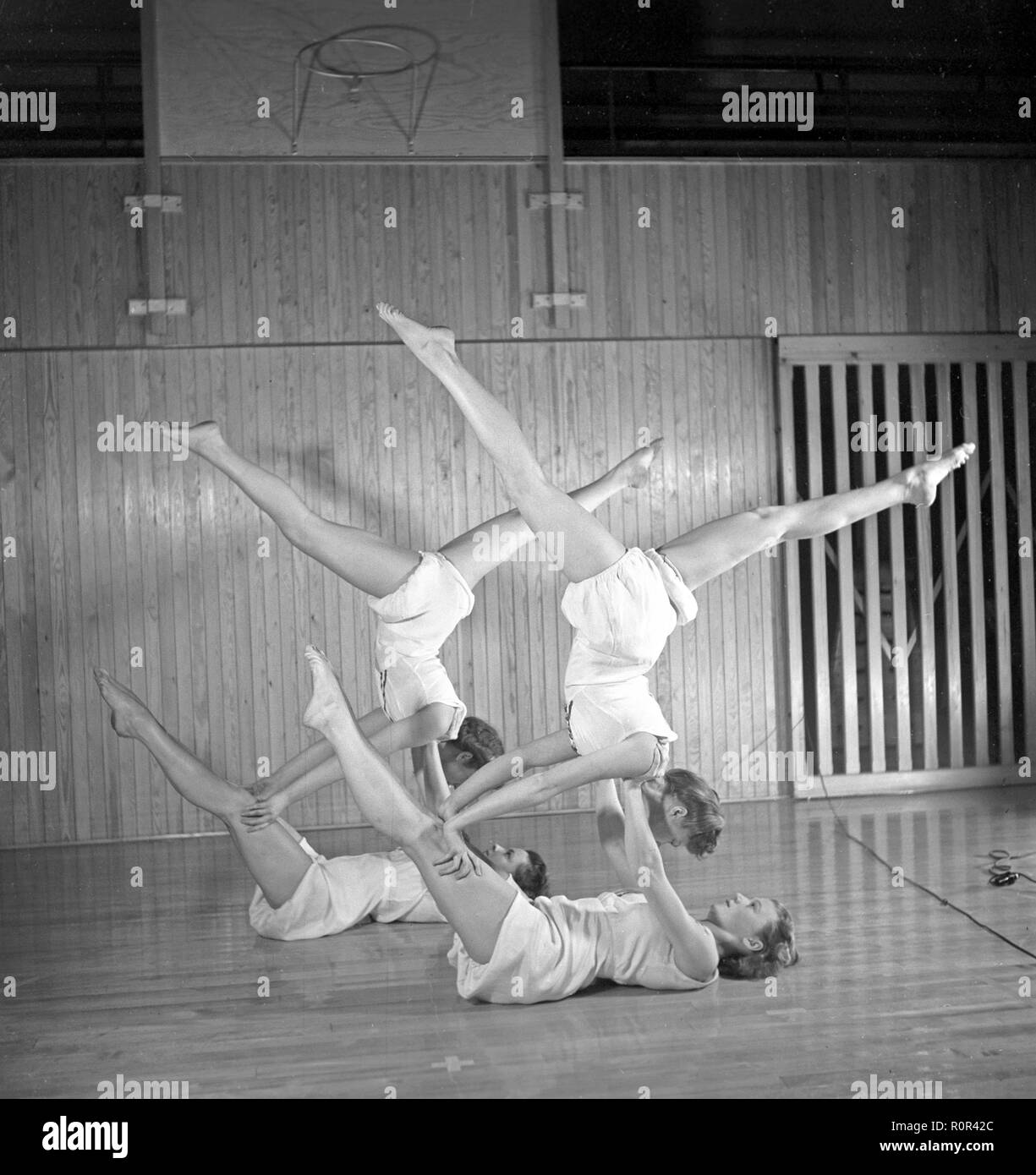 Gymnastics in the 1940s. Four young female gymnasts are practicing together and doing the same movement. 1940s Sweden Photo Kristoffersson ref M106-6 - Stock Image