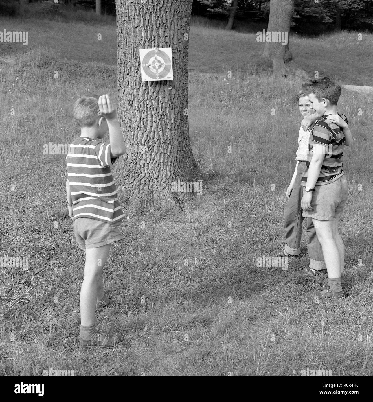 Summer activitiy in the 1950s. Three boys are playing darts outside.   Sweden 1957 Ref 3480 - Stock Image