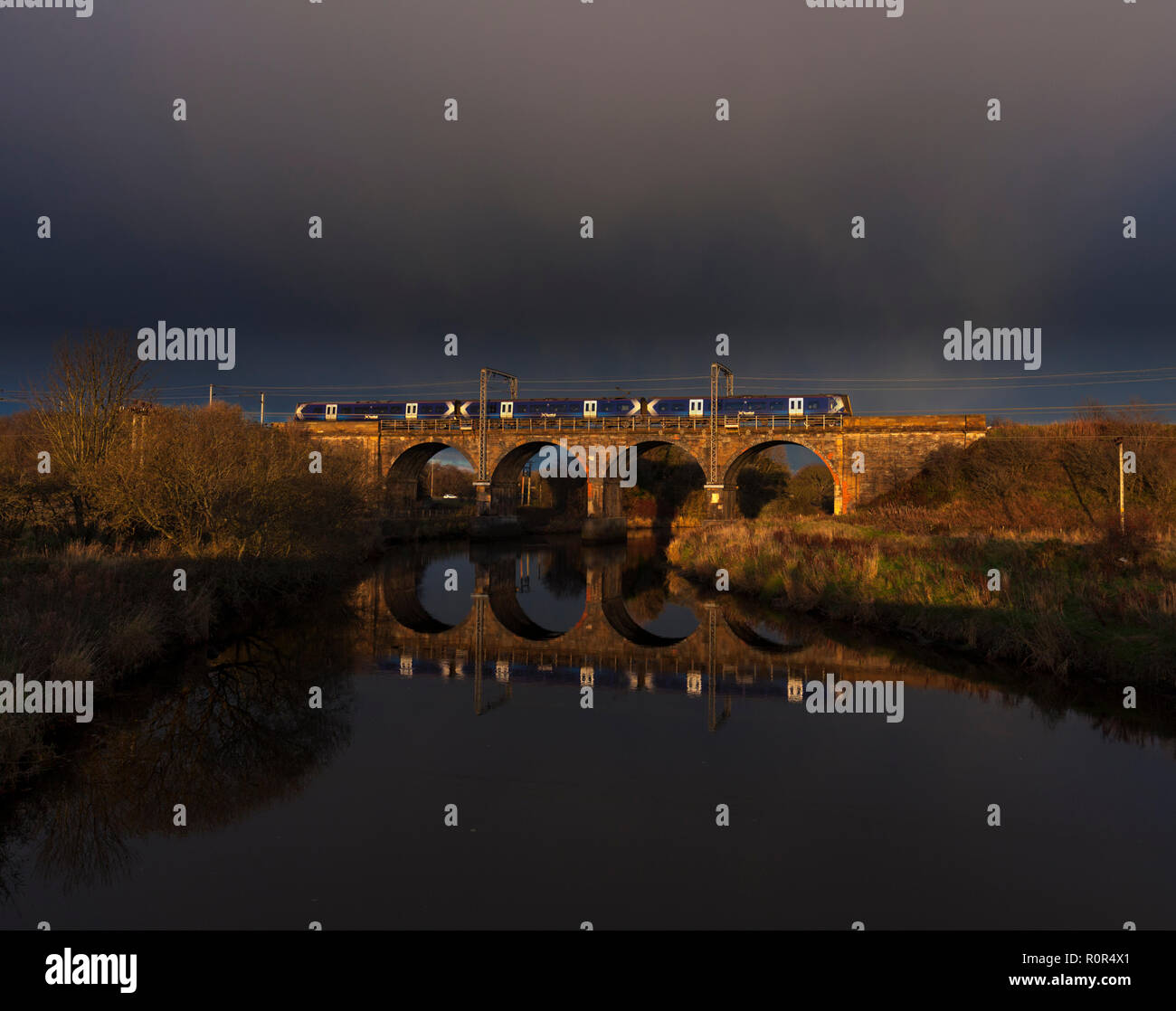 A Scotrail class 380 electric train crossing Garnock Longford viaduct (south of Kilwinning, river Garnock) with black clouds,  sunshine reflecting. - Stock Image