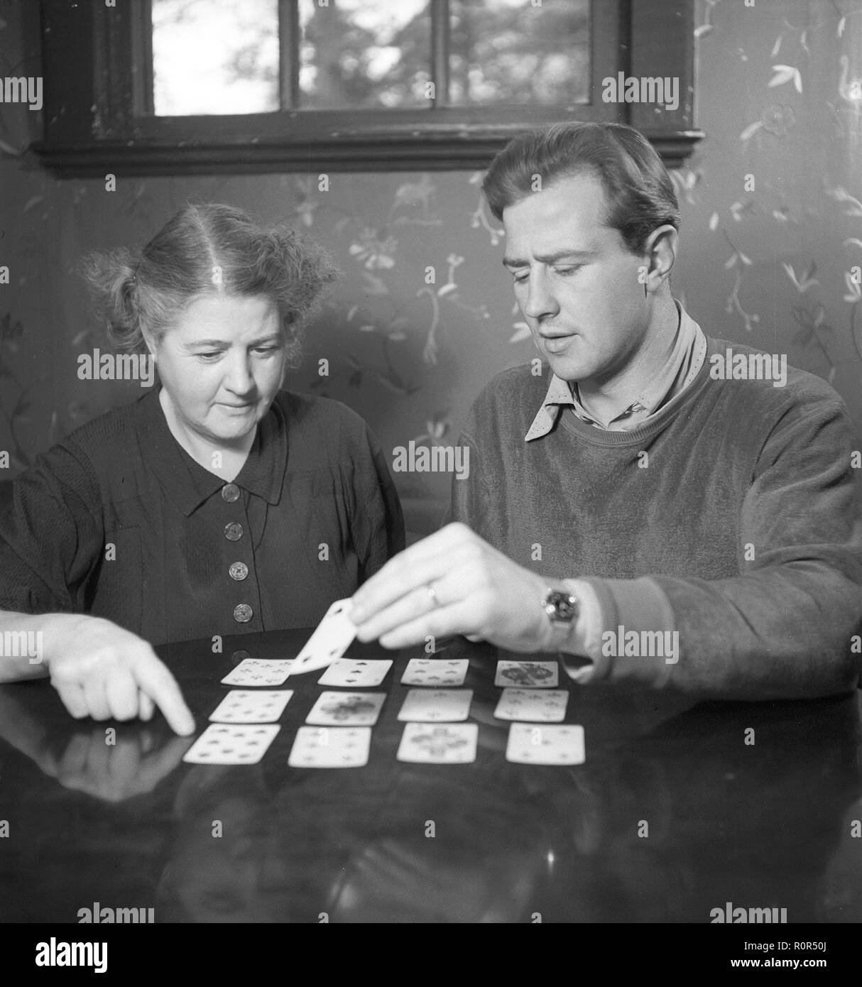 Playing solitaire in the 1940s. Swedish European boxing champion Olle Tandberg , 1918-1996. Pictured her with his mother playing solitaire. Sweden 1940s. Photo Kristoffersson Ref B140-1 - Stock Image
