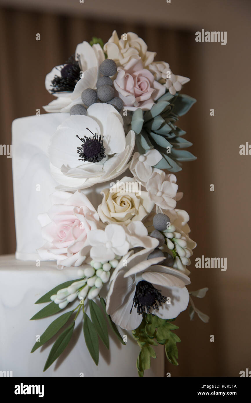 close up of icing flowers on a wedding cake. - Stock Image