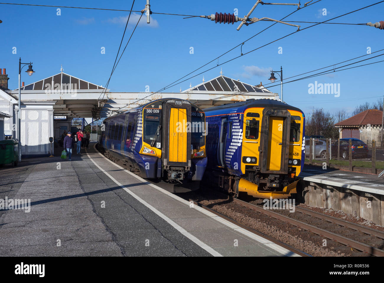 Scotrail class 156 diesel sprinter train and class 380 electric train at Troon railway station on the Ayrshire coast railway line, Scotland, UK - Stock Image