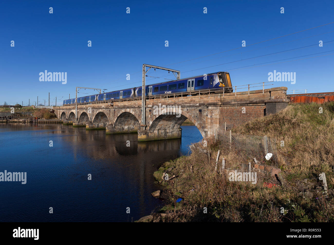 A Scotrail class 380 electric train crossing Queens Viaduct, Irvine,  over the river Irvine in Ayrshire  on the Ayrshire coast line. - Stock Image