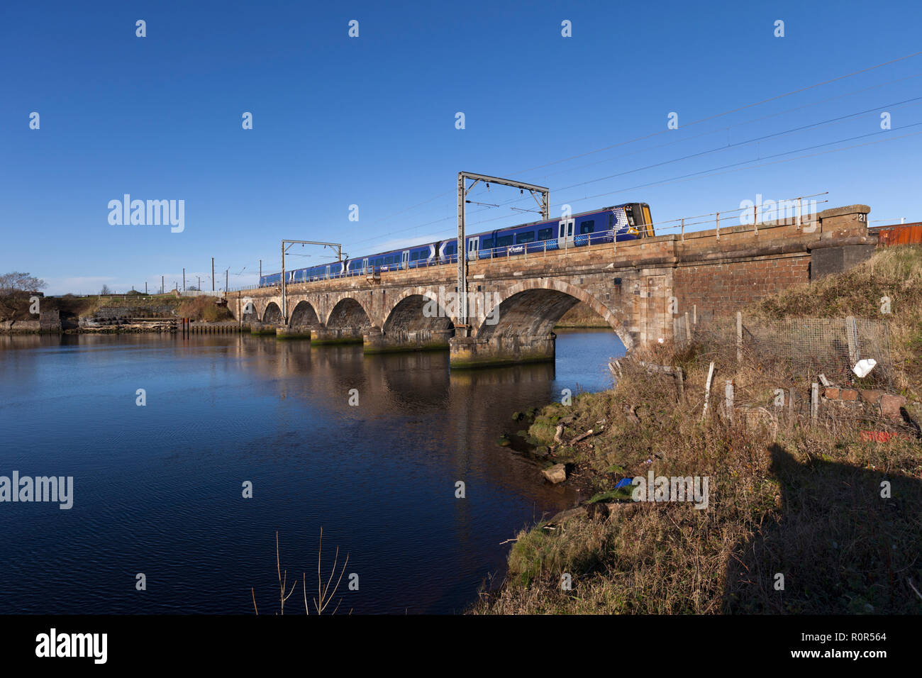 A Scotrail class 380 electric train crossing Queens Viaduct, Irvine Ayrshire, Scotland over the river Irvine on the Ayrshire coast line - Stock Image
