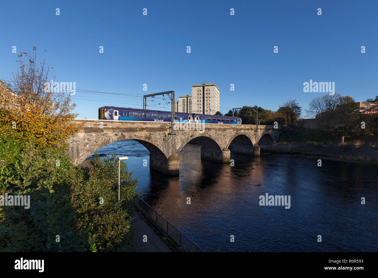 A Scotrail class 156 diesel sprinter train arriving at Ayr crossing the viaduct over the river Ayr - Stock Image