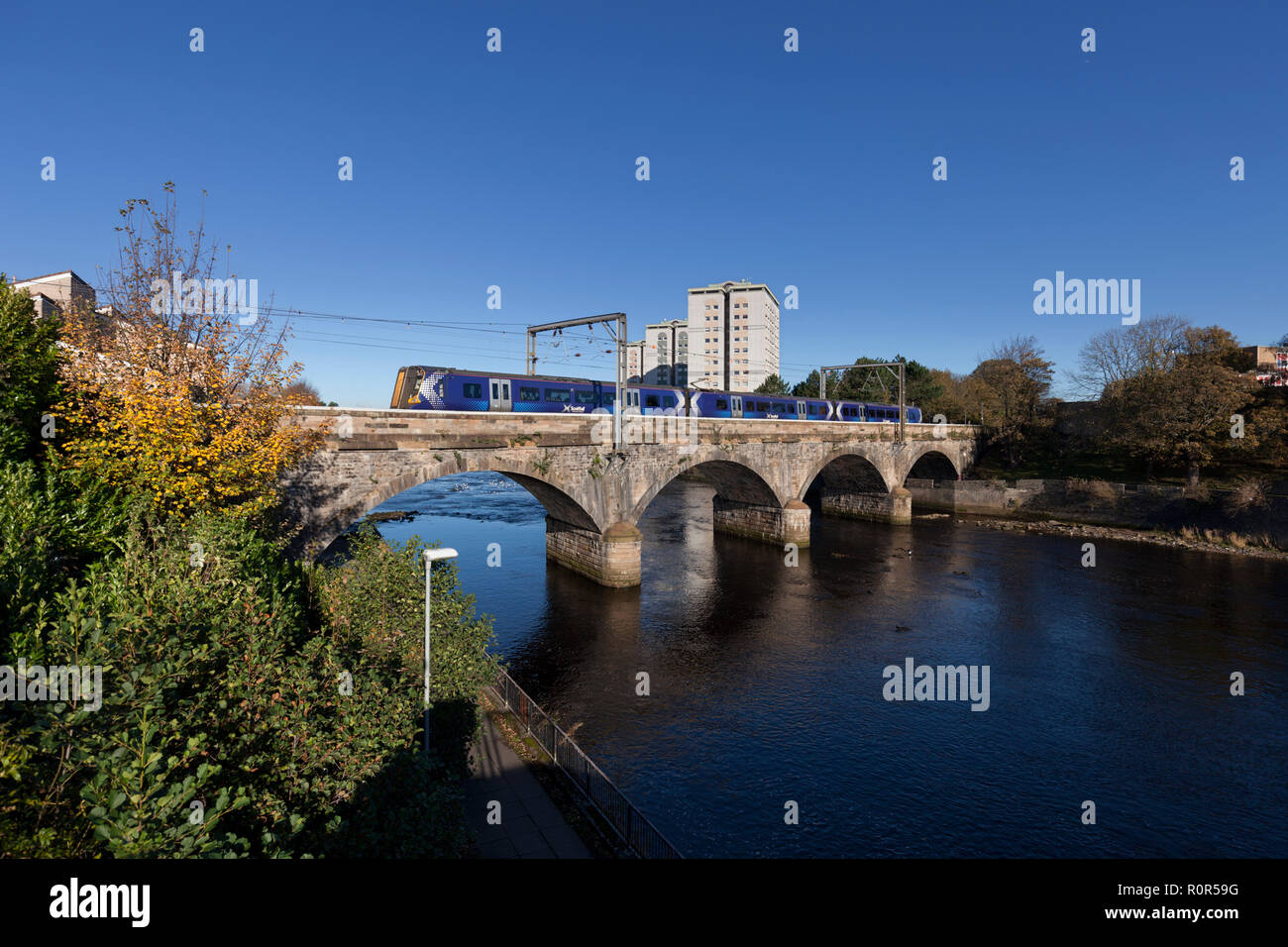 A Scotrail class 380 electric train departing  Ayr crossing the viaduct over the river Ayr - Stock Image