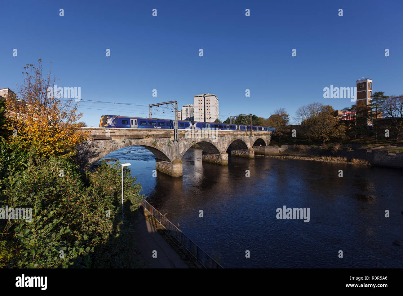 A Scotrail class 380 electric train arriving at Ayr crossing the viaduct over the river Ayr - Stock Image