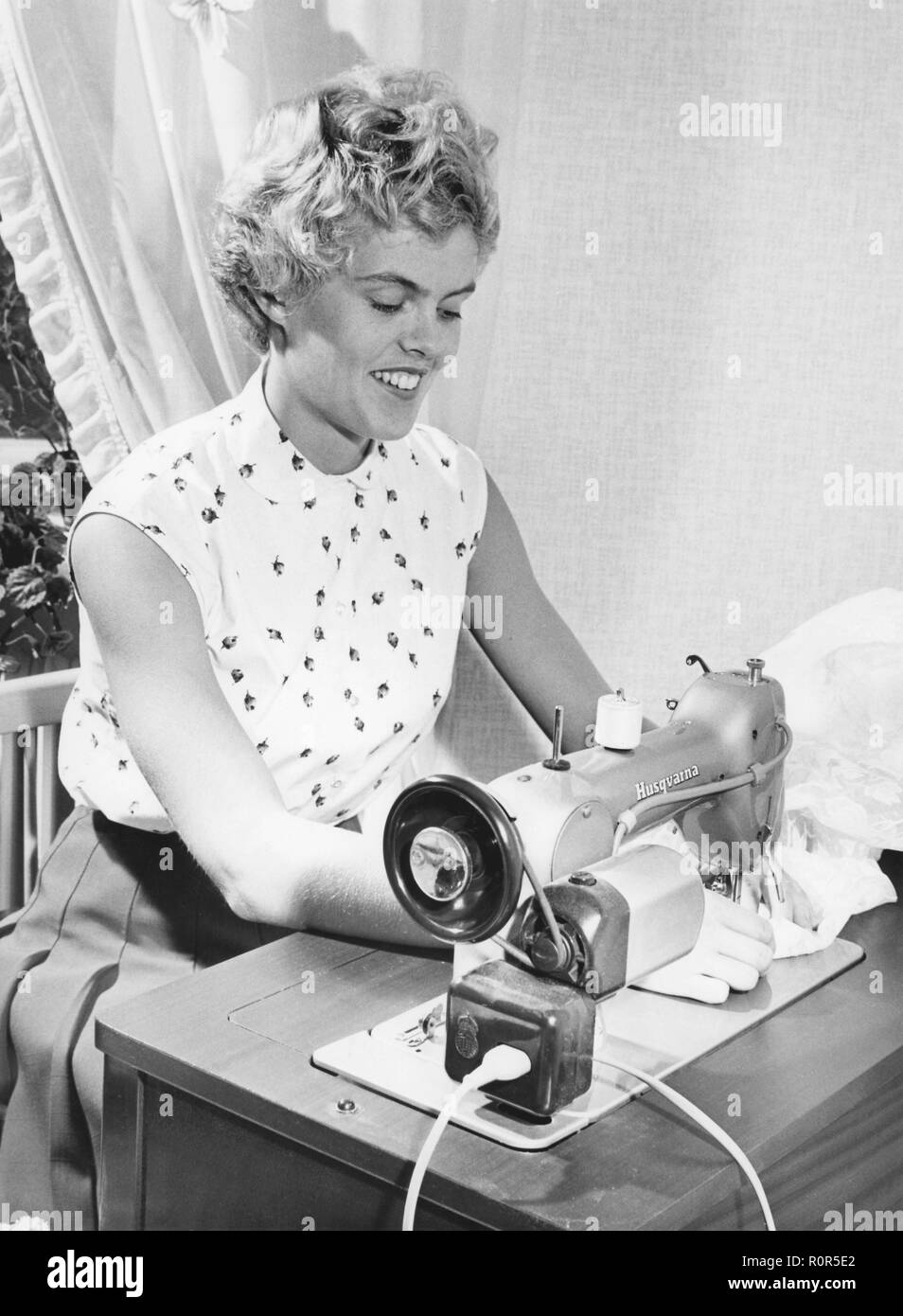 Sewing in the 1950s. Swedish female athlete and high-jump champion Inga-Britt Lorentzon at her sewing machine, a swedish model from manufacturer Husqvarna. - Stock Image