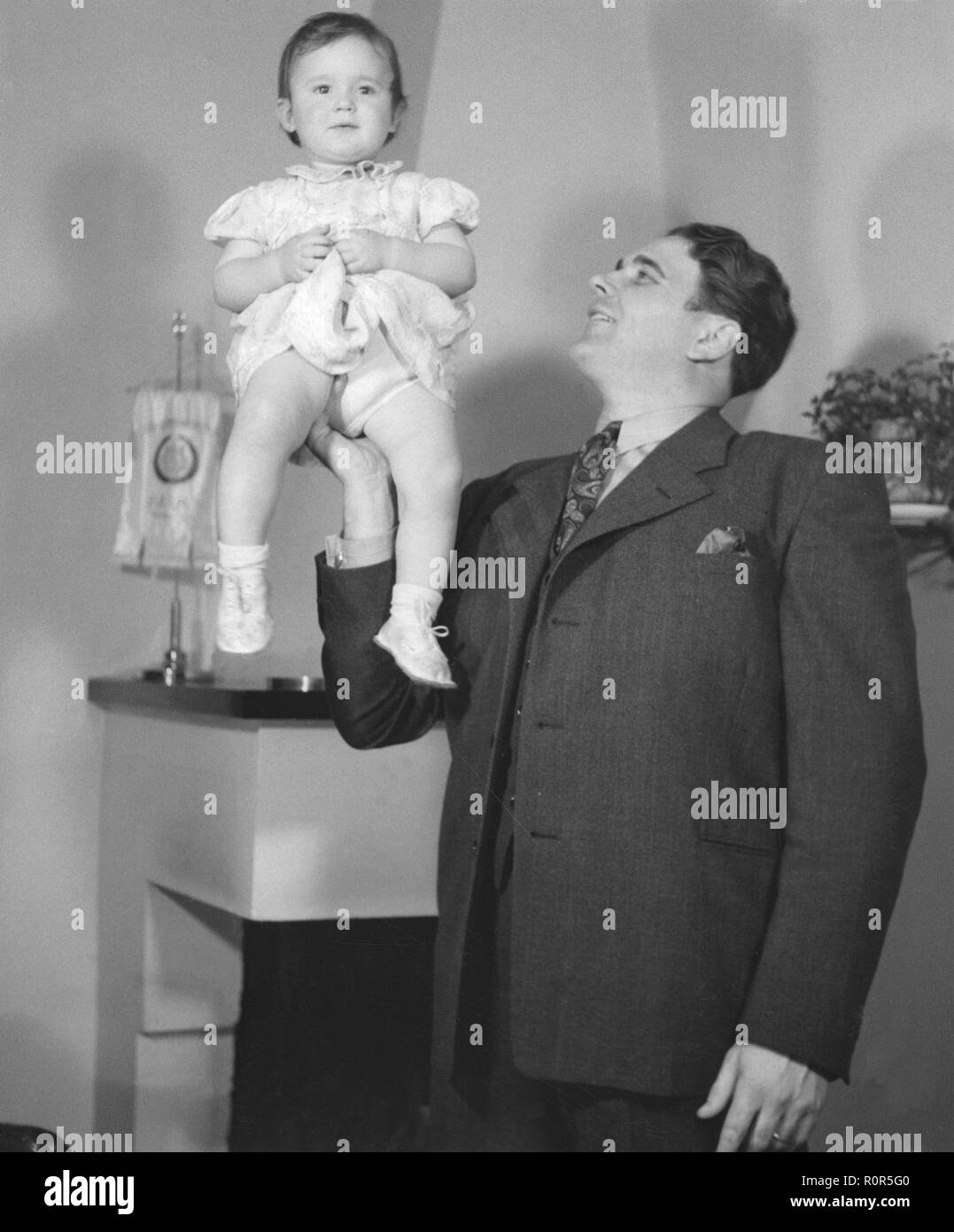 Father and child. Opera singer Erik Konrad 'Conny' Söderström (1911 -1972) with his child whom he is balancing on his arm and hand. Sweden 1940s - Stock Image