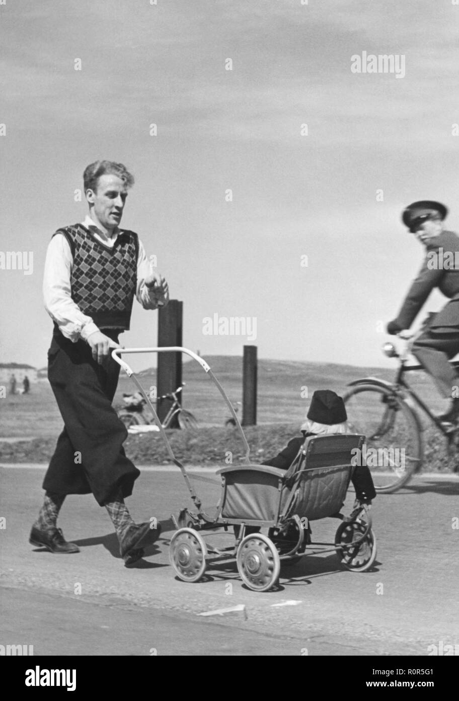 Father and child in the 1940s. A man wearing typical 1940s trouser fashion is pushing a stroller with his child in it. He is marching for a charity event 1942 - Stock Image