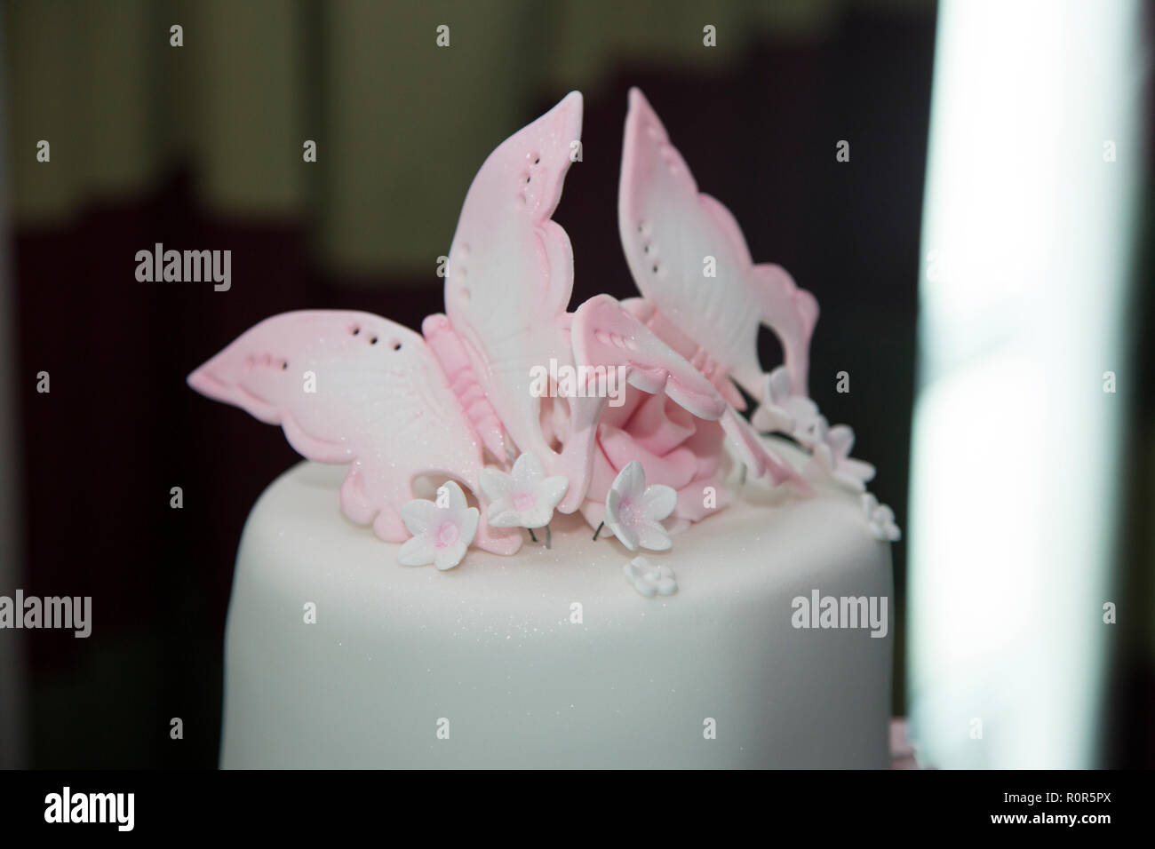 close up of white iced tiered wedding cake with pink decoration on - Stock Image