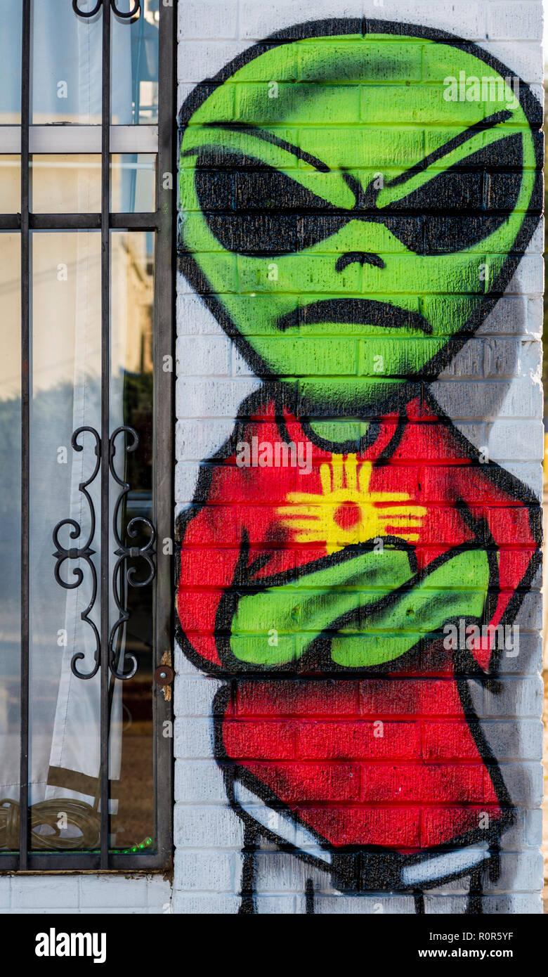 878c2e1ad27 Green alien with large black eyes wearing a red t-shirt with a Zia symbol