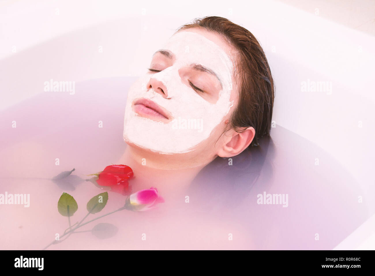 Redhead model using a homemade face mask with rose and coconut oil - Stock Image