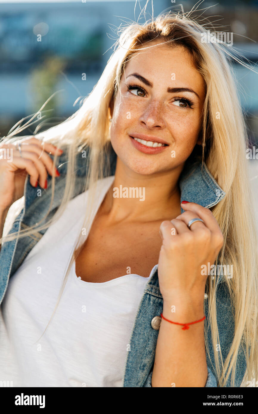 Portrait of happy blonde woman on blurred background in city - Stock Image