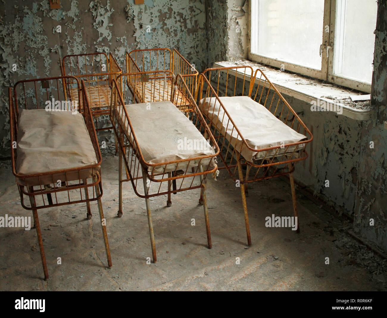 Nursery beds for newborn babies in deserted hospital in Pripyat, Chernobyl Exclusion Zone, Ukraine. - Stock Image