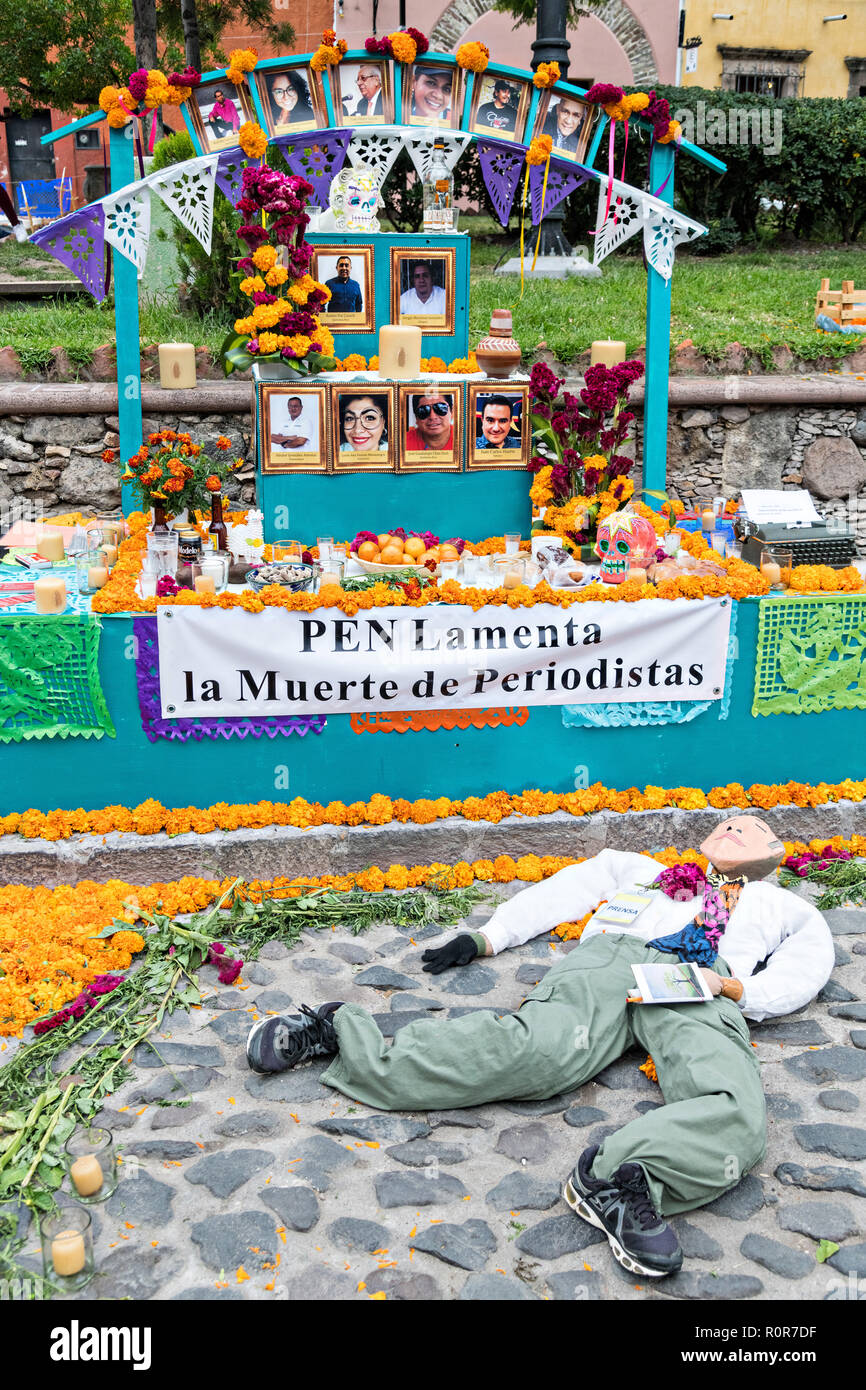 A Dead of the Dead altar known as an ofrenda dedicated to journalists killed during the Drug Wars in Mexico created by the PEN writers group during the Dia de Muertos festival in San Miguel de Allende, Mexico. The multi-day festival is to remember friends and family members who have died using calaveras, aztec marigolds, alfeniques, papel picado and the favorite foods and beverages of the departed. - Stock Image