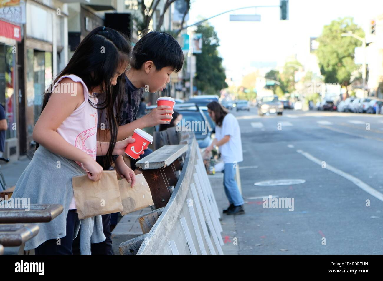 Two Asian children (a boy and a girl) stand at a sidewalk cafe overlooking a street blowing cool air on their hot chocolate; street scene. - Stock Image