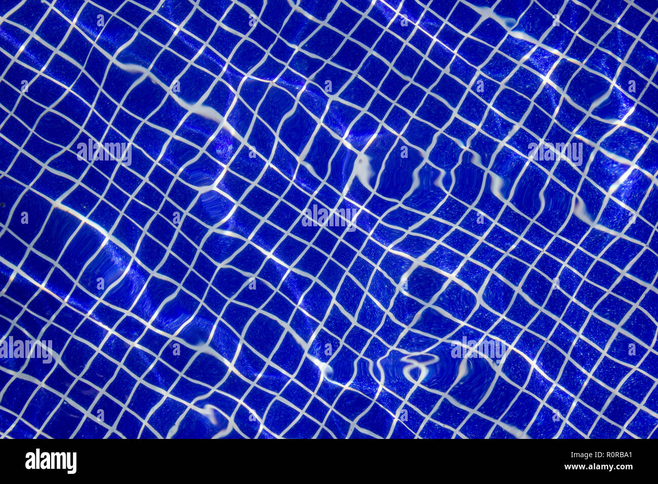 Detail of a symmetric texture deep on a pool made by the structural tiles used to build it and the water refraction of light - Stock Image