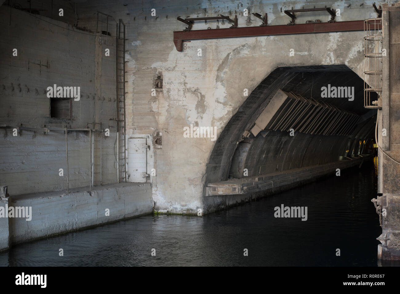 the entrance to the concrete bunker with the entrance from the water side. entry for ships - Stock Image