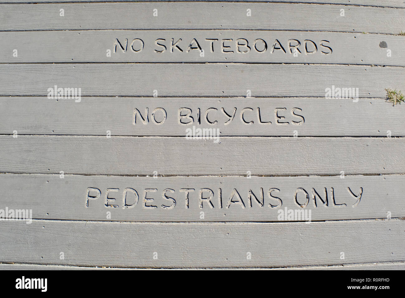 Restrictions carved into a boardwalk - No Skateboards, no bicyckes, pedestrians only - Stock Image