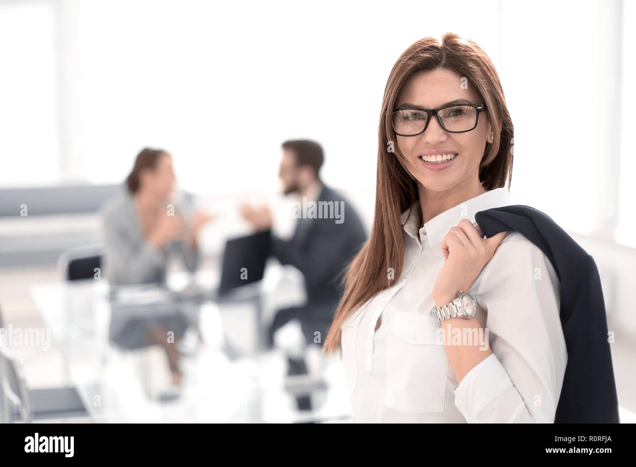 smiling business woman standing with a jacket over her shoulder - Stock Image