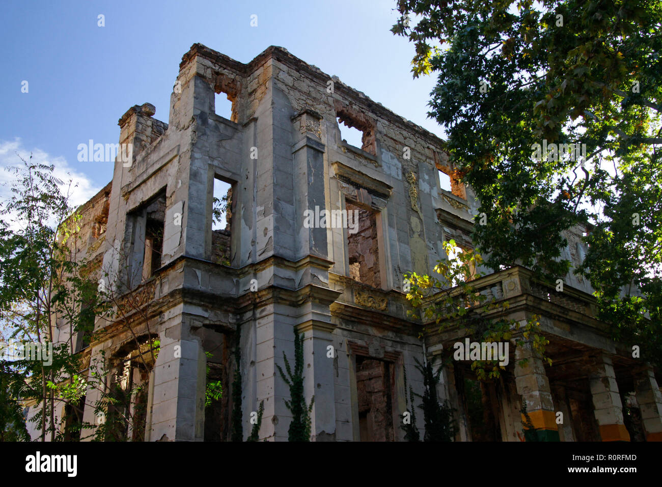 Remains of the war in Mostar, Bosnia and Herzegovina: Ruin without a roof with trees growing inside of it - Stock Image
