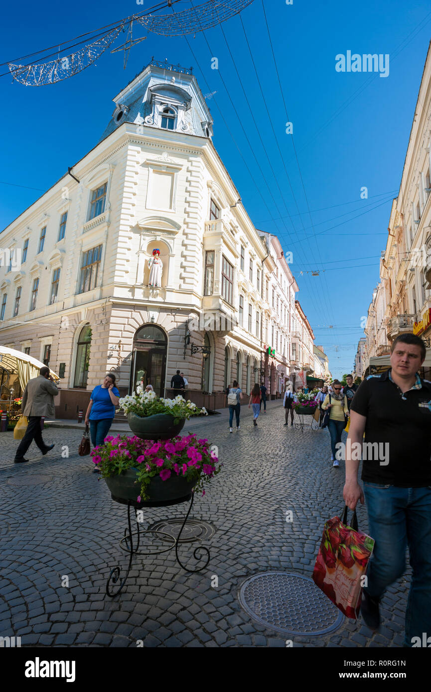 Pedestrians on Olha Kobylyahska Street in Chernivtsi, a superb example of Austro-Hungarian Empire architecture in western Ukraine. - Stock Image