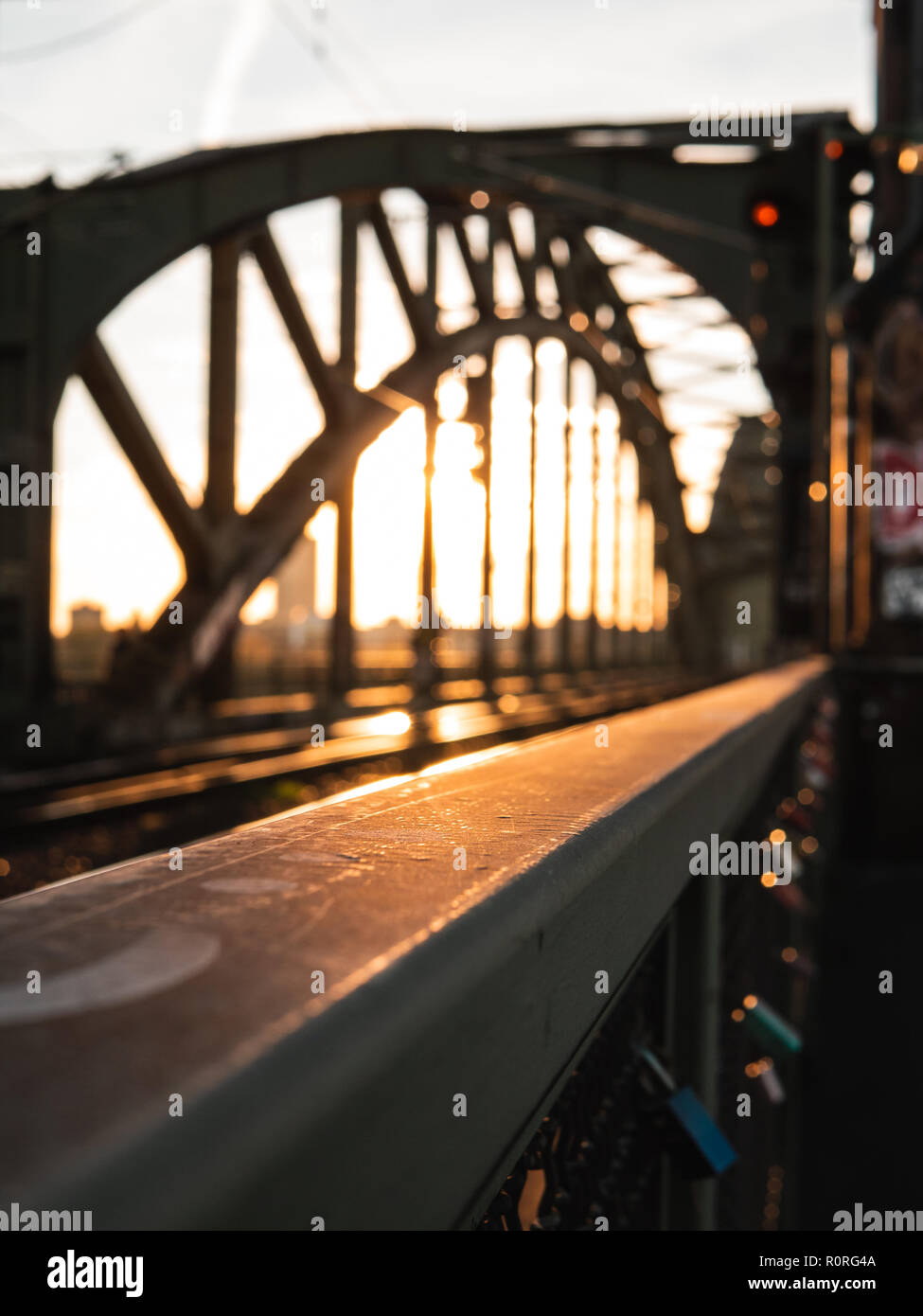 Railings of a bridge at sunset, with bridge blurred in background. Cologne, Germany. - Stock Image