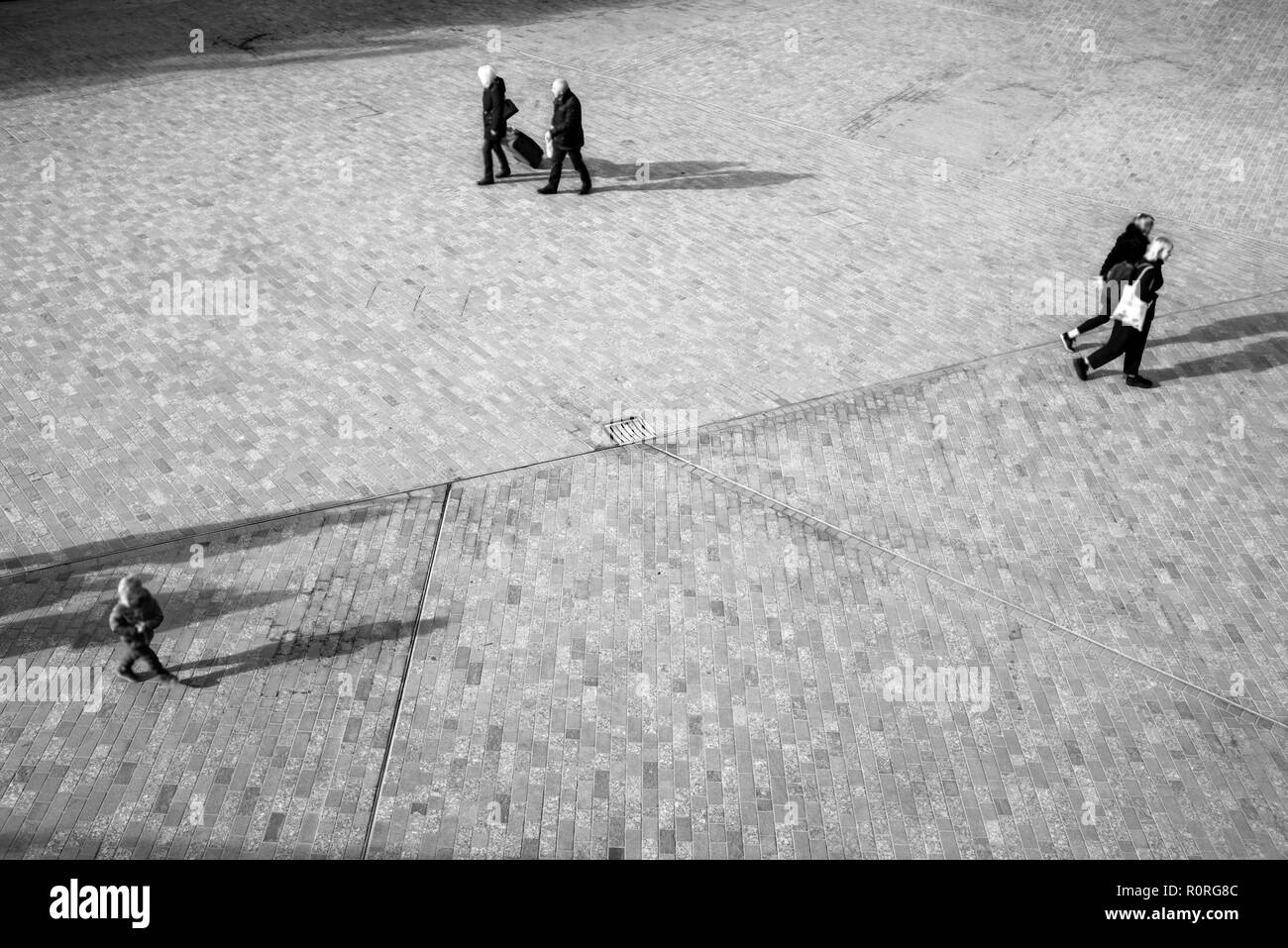 Blurred unrecognizable people from above walking on an open space square with shadows projecting on the floor - Stock Image