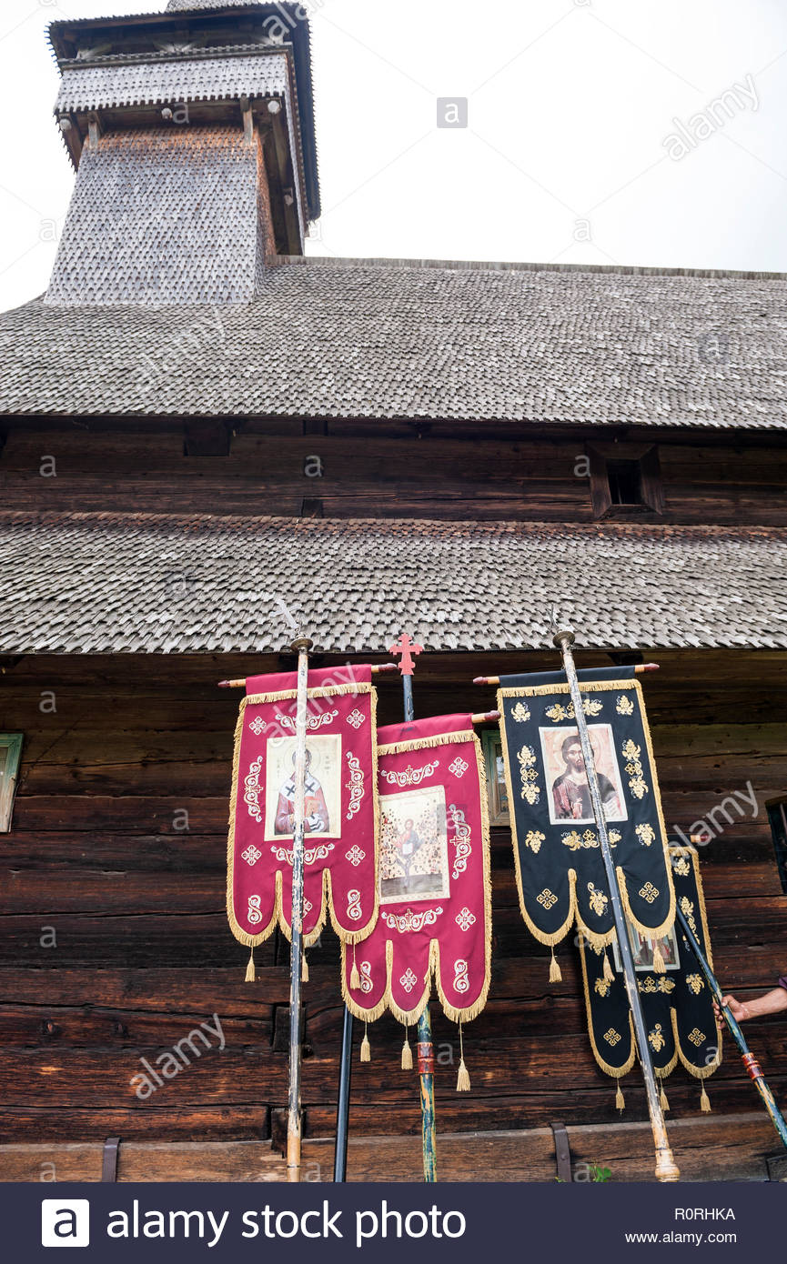 Banners used for a Pentecost procession outside the wooden church in Poienile Izei in the Maramureș region in Romania. - Stock Image
