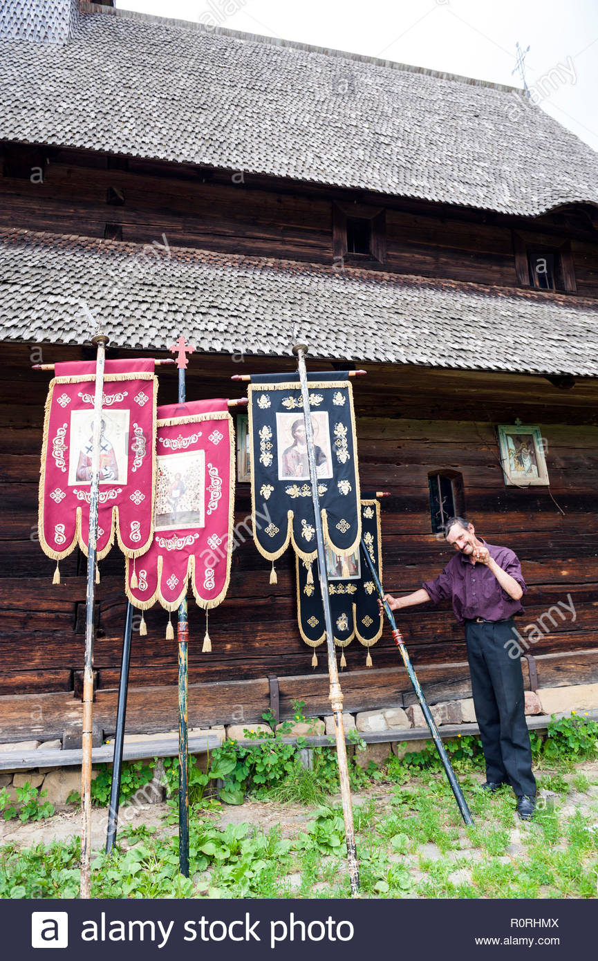 A man holds banners used for a Pentecost procession outside the wooden church in Poienile Izei in the Maramureș region in Romania. - Stock Image