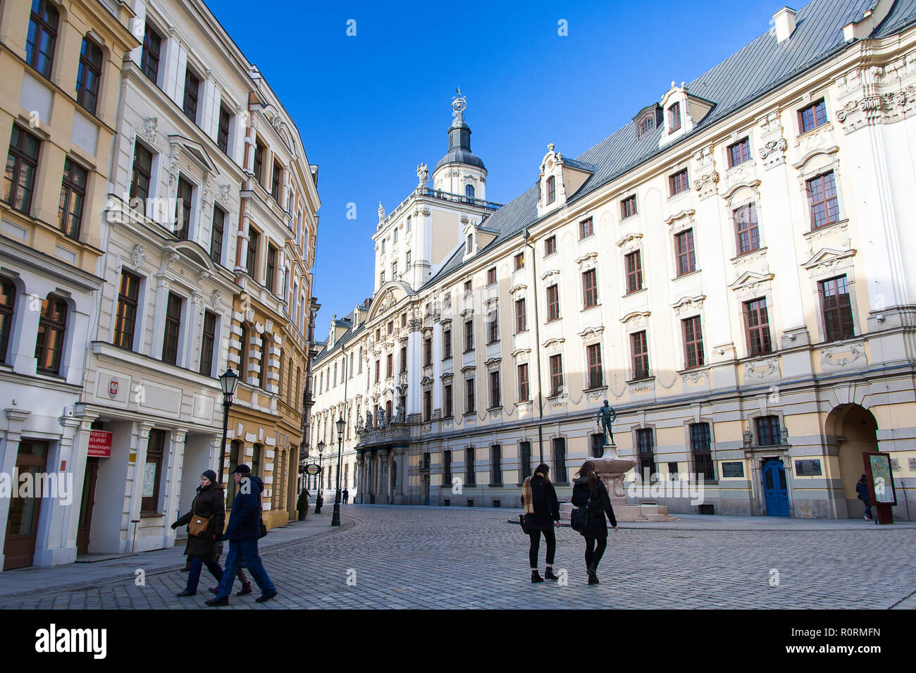 Pedestrains walk along the street in front of the University of Wroclaw, main building.  Magnificent Baroque facade  with clear blue sky background - Stock Image