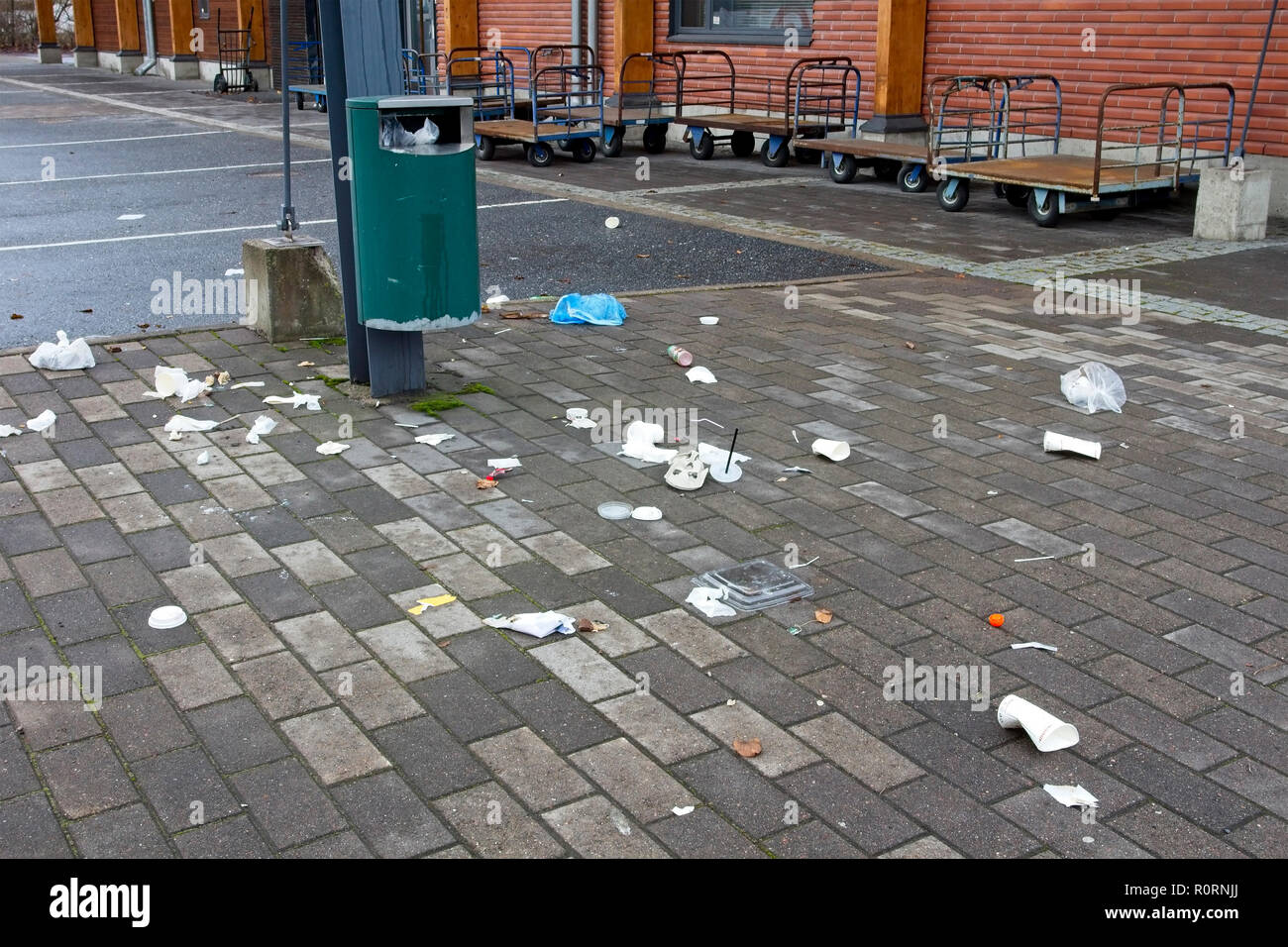 littered area with trashcan - Stock Image