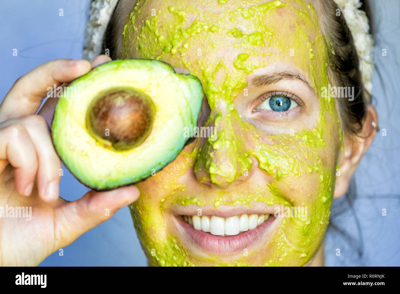 Twenties female with an avocado face mask. - Stock Image