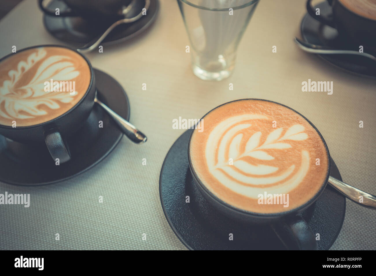 Hot art latte coffee in a cup on wooden table and coffee shop blur background with bokeh image. Latte art coffee table top view, happy relaxing mood - Stock Image