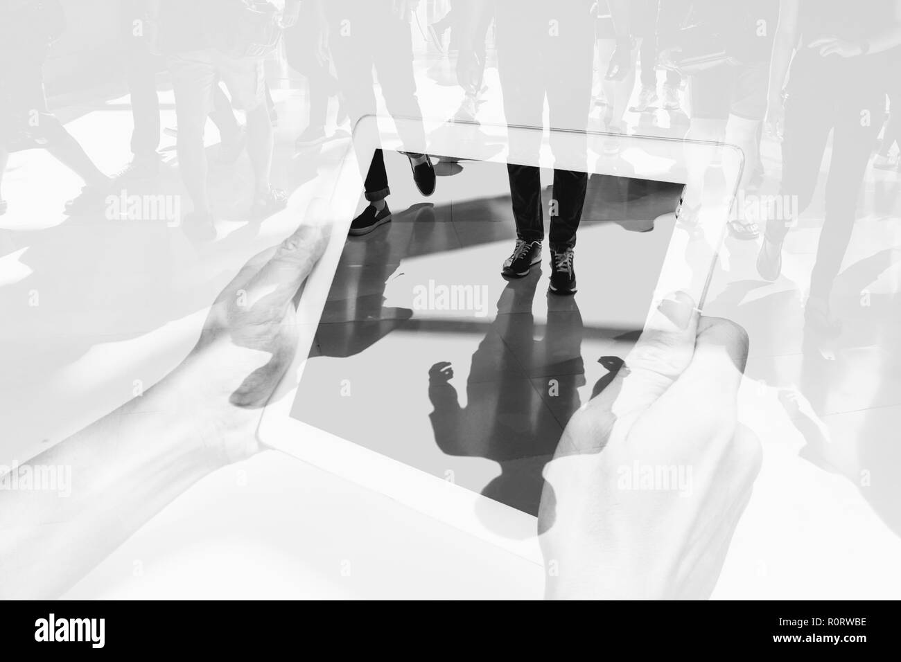 Double exposure people walking and hands holding white tablet pc. Representing modern urban life with connection and communication technology. - Stock Image