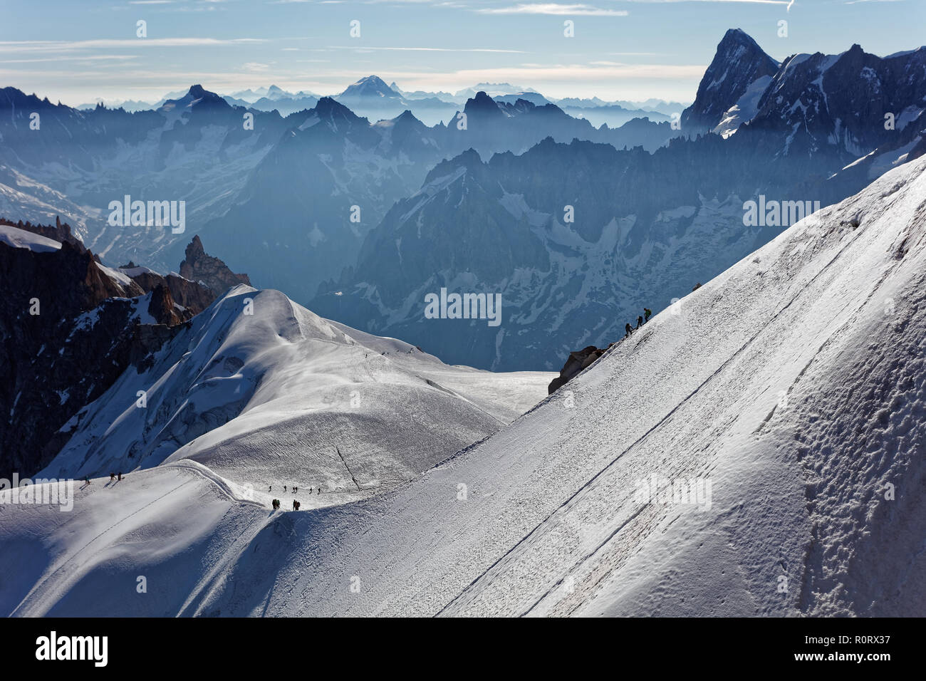 Chamonix, south-east France, Auvergne-Rhône-Alpes. Climbers heading for Mont Blanc. Descending from Aiguille du Midi cable car station towards sunny s - Stock Image