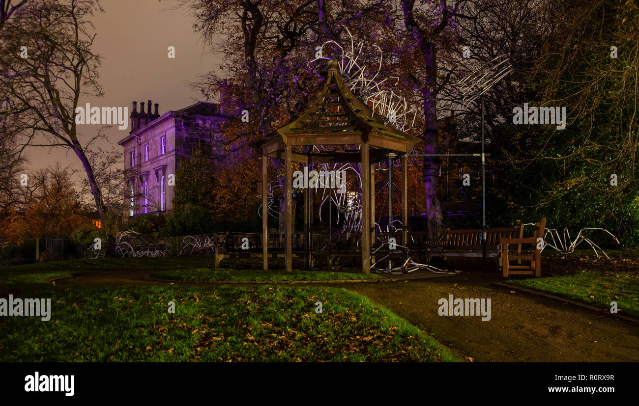 Eerie colours, a mansion and spiders made from lights, at GlasGLOW, where the Botanic Gardens are lit up at night. - Stock Image