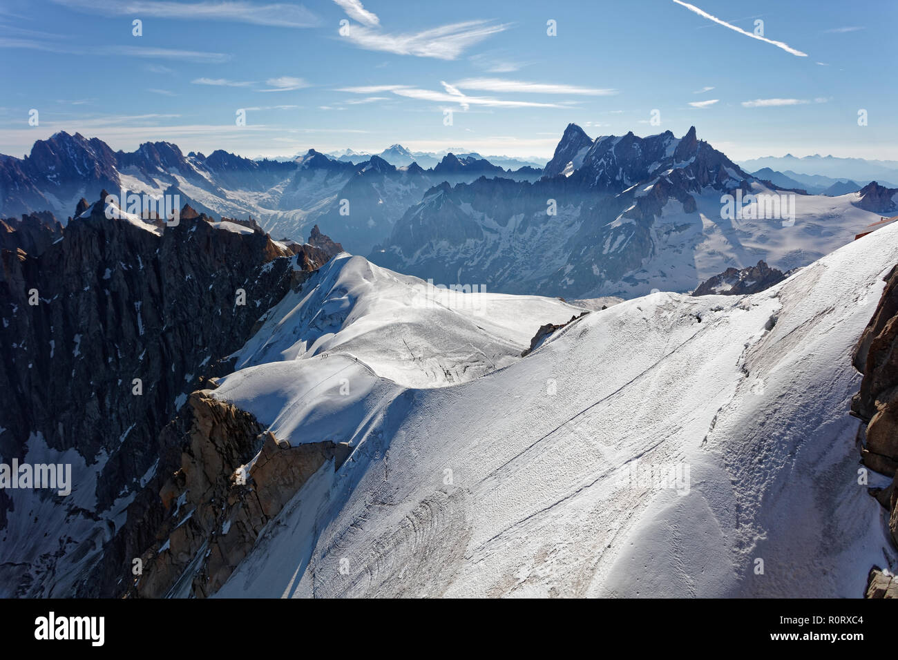 Chamonix, south-east France, Auvergne-Rhône-Alpes. Climbers heading for Mont Blanc. Descending from Aiguille du Midi cable car station towards sunny s Stock Photo