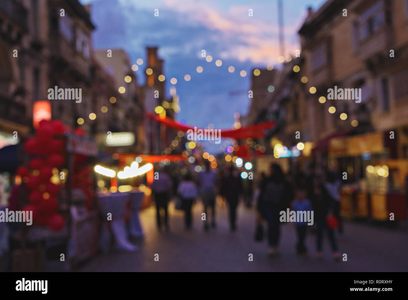 Blurred background of Christmas fair on old town street. Traditional Christmas market time concept with colorful Christmas lights - Stock Image